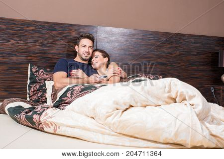 Beautiful young couple watching TV in Bed.