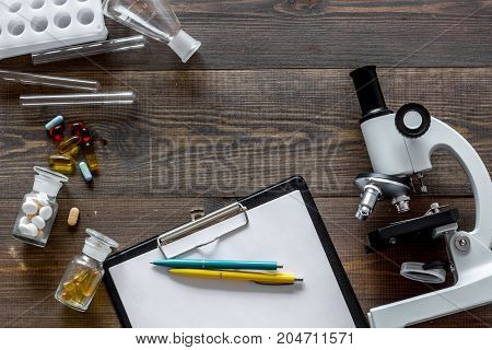 Microscope, pills and tablet on wooden background top view.
