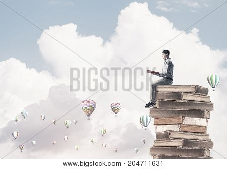 Young shocked man sitting on pile of books with one in hands