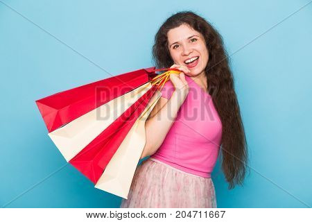 Portrait of young happy smiling woman with shopping bags, over blue background. Purchase, sale and people concept.