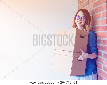 Woman In Jeans Shirt Standing On Brick Wall With Moving Boxes