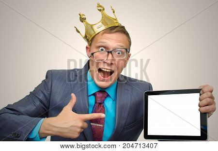 Best offer. Big sale. Product presentation. Promotion. Funny mad Man in suit and glasses holding in hands tablet PC with blank screen and showing on mobile device by finger.