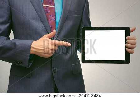 Product presentation. Promotion. Market research. Business man holding in hands tablet PC with blank screen and showing on device by finger close up.
