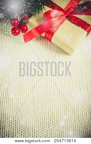 Christmas background with decorations and gift boxes on knitted board blanket. Xmas presents with blank postcard. Snow Falling Effect.