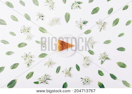 Top view of a slice of pie on a white table amongst green flowers