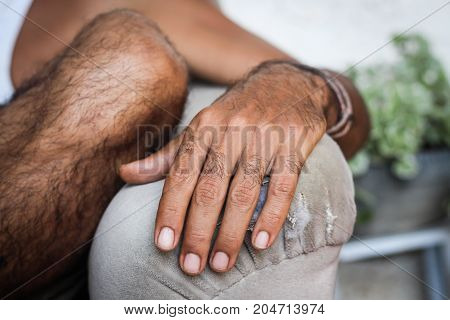 A man's hand laid on the couch handle very calmly