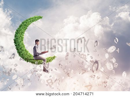 Young man in casual sitting on green moon with red book in hands