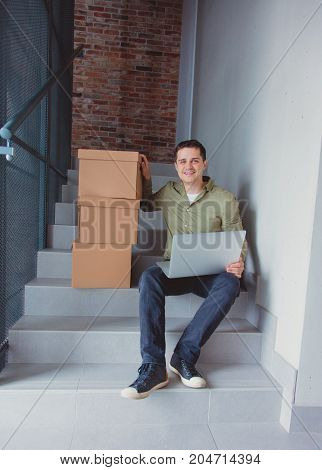 Handsome Man With Moving Boxes And Laptop Sitting On Stairs