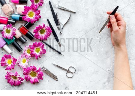 Preparing for manicure. Tools and nail polishes on grey background top view.