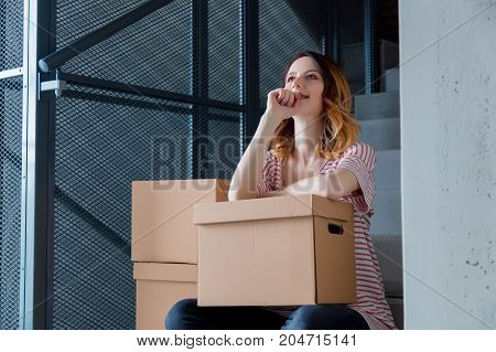Woman With Moving Boxes Sitting On Stairs In House