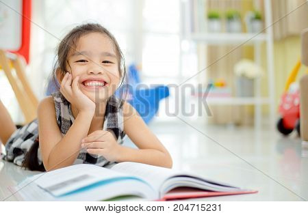 Cute asian girl reading a book and smiling teeth white while in the live room.