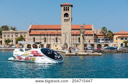 RHODES, GREECE - AUGUST 2017: Excursion boat is driving along old Venetian watch tower at old seaport of Rhodes island, Greece