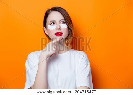 Woman Using Eye Patch For Her Eyes On Orange Background Isolated