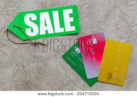 Sale concept. Sale label near bank cards on light stone background top view.
