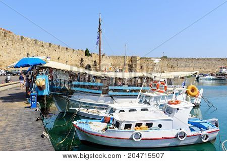 RHODES, GREECE - AUGUST 2017: Traditional Greek fishing boats are staying moored at sea port of Rhodes town on Rhodes island, Greece