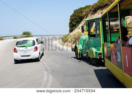 RHODES, GREECE - AUGUST 2017: Curvy road with white car and funny excursion train on Rhodes island.