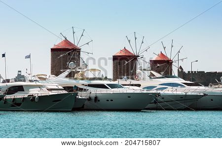 Ancient windmills and yachts in port of Rhodes town on Rhodes island, Greece