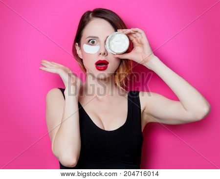 Woman Using Eye Patch For Her Eyes And Cream On Pink Background