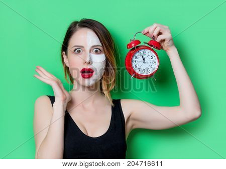 Woman Using Eye Patch For Her Eyes Holding Alarm Clock.