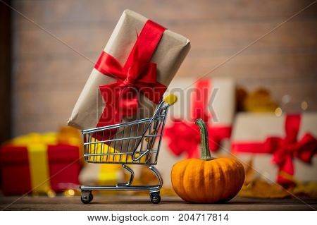 Cart Full Of Gifts For Halloween Near A Little Pumpkin