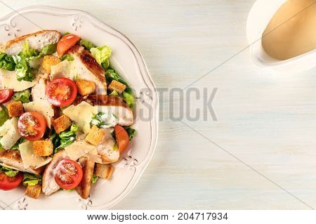 An overhead photo of a plate of chicken Caesar salad on a light background with a gravy boat, and copy space