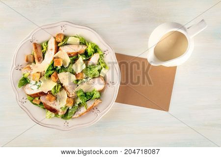 An overhead photo of a plate of chicken Caesar salad on a light background with a gravy boat, and a piece of brown paper for a recipe, or just copy space
