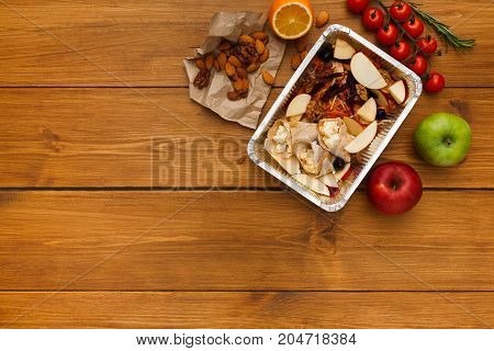 Healthy food delivery background. Lunch box with apples, nuts and salad on rustic wood table, copy space