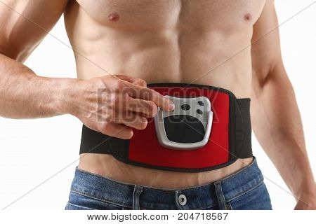 Athletic Folded Man Uses An Electric Belt Simulator For Training A Press