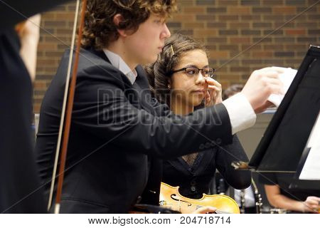 ROMEOVILLE, ILLINOIS / UNITED STATES - MAY 21, 2017: Violinists of the Metropolitan Youth Symphony Orchestra (MYSO) perform music in a concert in Borromeo Hall at Lewis University.