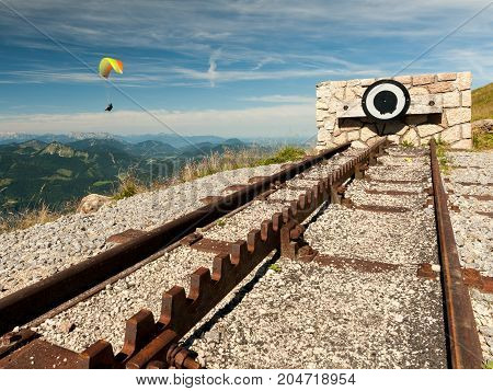 Endpoint of a rack railway on the top of a mountain on a sunny day with a paraglider in the background
