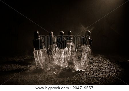 Vape Concept. Smoke Clouds And Vape Liquid Bottles On Dark Background. Light Effects. Useful As Back