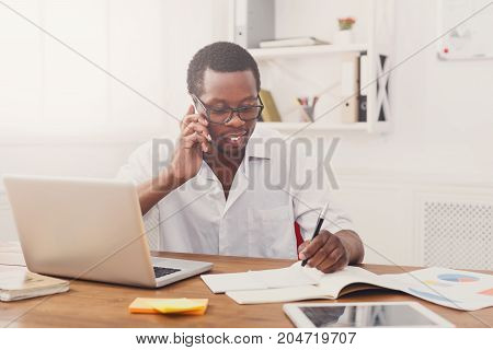 Black businessman discussing on cellphone and taking notes in modern office, copy space