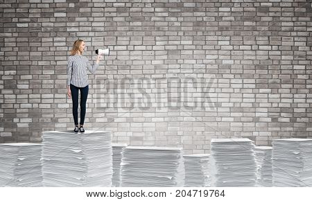 Woman in casual clothing standing on pile of documents with speaker in hand with grey brick wall on background. Mixed media.