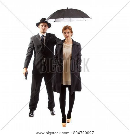 A fancy lady being escorted by a man in a suit holding a gun and an umbrella