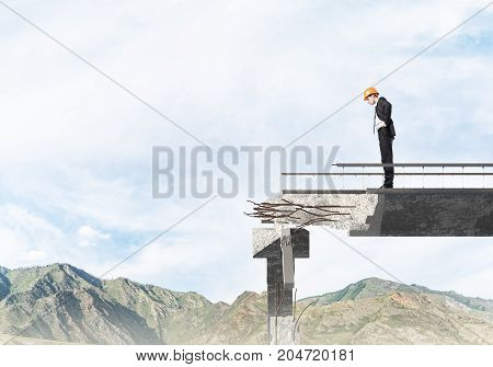 Young engineer in suit and helmet looking down while standing on broken bridge with skyscape and nature view on background. 3D rendering.