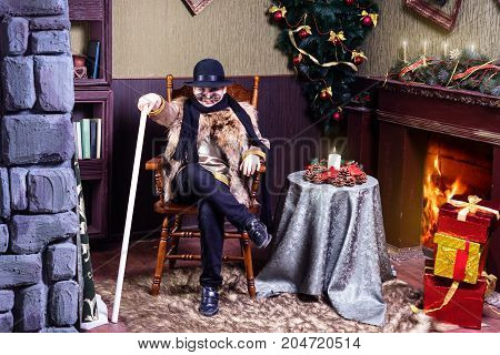 Studio shot of little boy wearing Basilio The Cat costume and sitting in front of fireplace