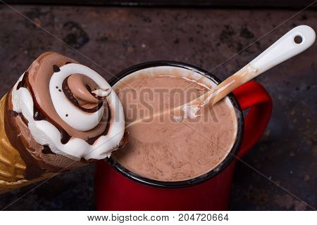 Wafer horn with chocolate ice cream and melted ice cream on grunge background