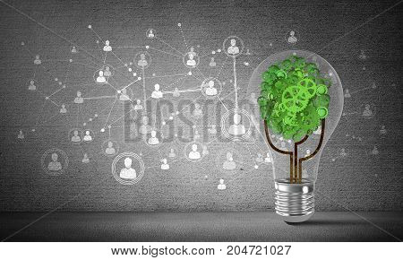 Lightbulb with tree from gears inside placed against social network system sketched on grey wall. 3D rendering.