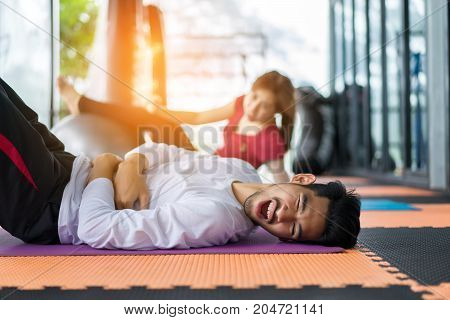 Young asian man and woman injured exercise erobics with yoga ball indoor for building muscle slim body and strong perfect