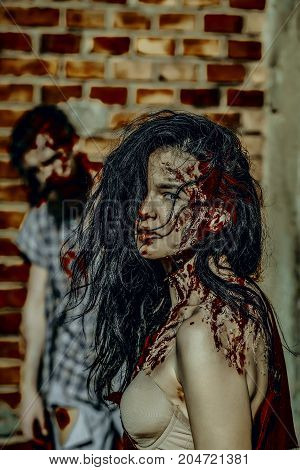 Halloween woman with bloody brunette hair. Zombie couple in torn clothes standing on brick wall. Blur man or war soldier with wounds. Holiday celebration concept. Girl vampire with red blood.