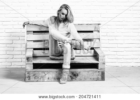 girl or beautiful cute woman sexy fashion model with blond hair in jeans casual clothes sits on wooden pallet sofa on brick wall black and white