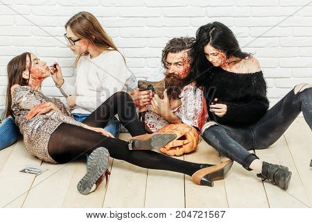 Halloween zombie people of bearded man long beard brutal caucasian hipster with moustache hold pumpkin axe and bloody women with wounds and red blood on white brick wall background