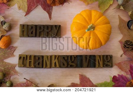 Happy Thanksgiving message with pumpkin and other autumn decorations