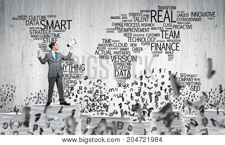 Businessman in suit standing among flying letters with speaker in hand with business-related terms in form of world map on background. Mixed media.