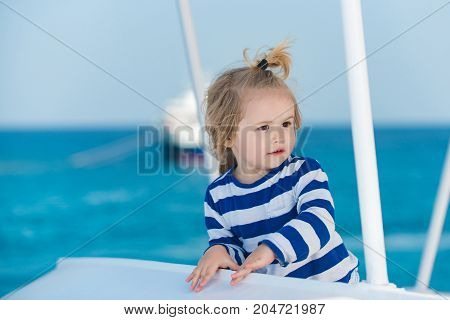 Child in striped shirt looking at blue ocean water. Summer trip and vacations. Boy little kid with cute serious face sailing on white ship. childhood and happiness concept. Sea voyage and cruise.
