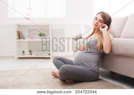 Pregnant woman listening to music in headphones. Young expectant blonde enjoying classical melody, copy space. Relax, leisure, pregnancy concept