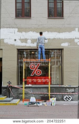 Moscow Russia - June 30 2015: Man plastering facade of the building in Moscow