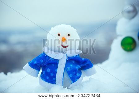 Snow Sculpture In Blue Coat On Winter Day Outdoors