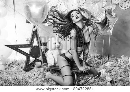 pretty woman or cute sexy girl in erotic lingerie of bra panties has red lips sitting on sledge at teddy bear toy festive golden balloons white snowflakes feathers. party and holiday celebration