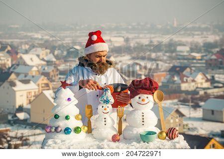 Cook, Snowmen And Snow Xmas Tree On Blue Sky